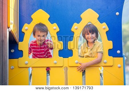 Cute Children, Boy Brothers, Peeks Through Hole At Playground Outdoors At Park