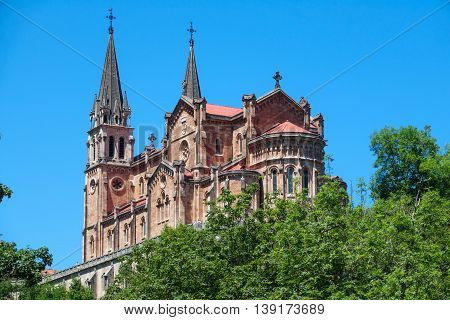 Closeup view of Basilica of Santa Maria in Covadonga over the trees, Asturias, Spain