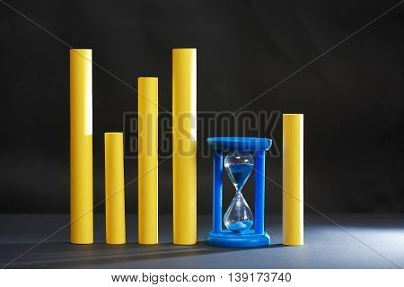 Abstract composition with blue hourglass near yellow sticks on dark