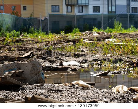 Rubbish dirty puddles in a vacant lot near the buildings. Construction garbage. Concept - urban ecology construction and environmental protection