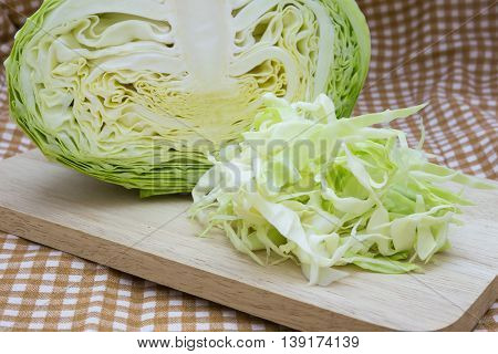 Closeup cabbage and cutted cabbage on wooden fabric scott pattern background