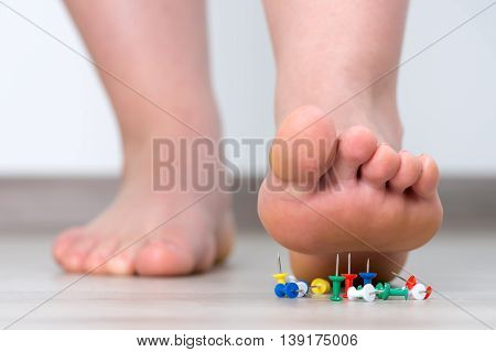 Female foot above colored pushpin. Closeup pin