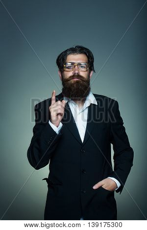 Handsome man bearded hipster male in vintage glasses suit points forefinger upwards on grey wall