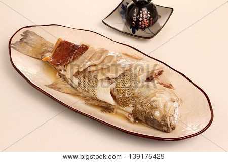 Steamed grouper in Japanese style on plate in restaurant
