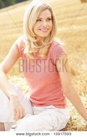 Woman Sitting On Straw Bales In Harvested Field