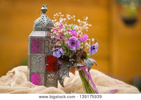 Garden style summer bouquet. Mix of lilac and purple anemone flowers, geranium flowers and heuchera or alumroot leaves. Bouquet with indian style lantern. Garden style wedding bouquet. Flower design.