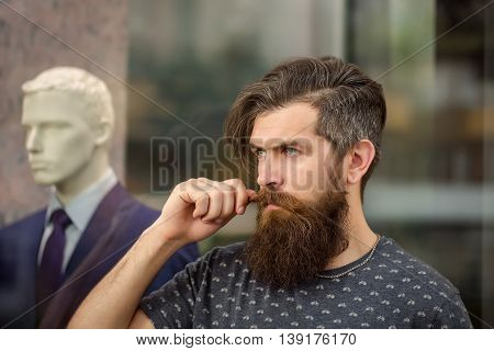 Bearded Man Near Showcase With Dummy