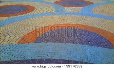 pattern of small, square, colored bricks making interlocking circles of blue, purple, orange, and yellow bands, on a beach plaza.