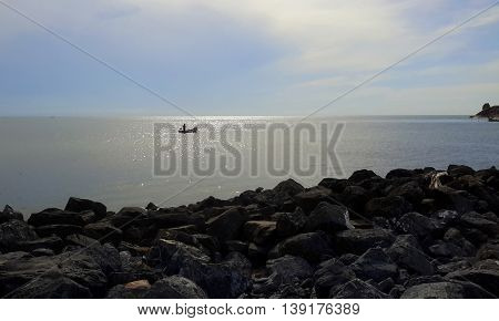 rocky shore in foreground, with distant man standing in fishing boat in sparkling sea, edge of peninsula seen on the right, blue sky, Songkhla, Thailand