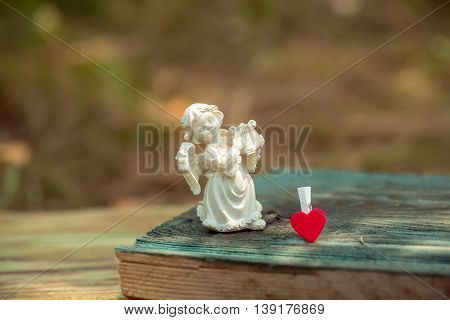 Beautiful angel playing harp white porcelain figurine and red heart clothespin on wooden board on natural background