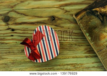 Gift box heart shaped of striped wrapper and red ribbon bow decoration on wooden plank on timber background