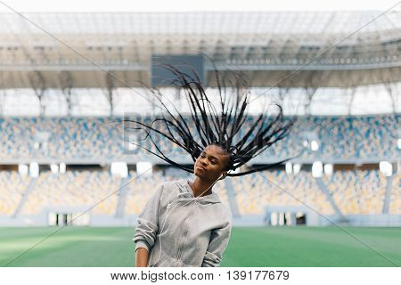 Charming African American woman listening to music on earphones swinging her braided hair on field stadium.