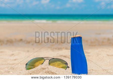 Sunglasses and sun cream on white  sand beach