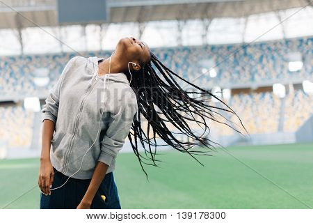 Young african american teenage girl in gray hoodie listening to music and playing with her hair at stadium.