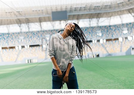 Beautiful young African American woman dancing as she throws her hair, listening to music with headphones.