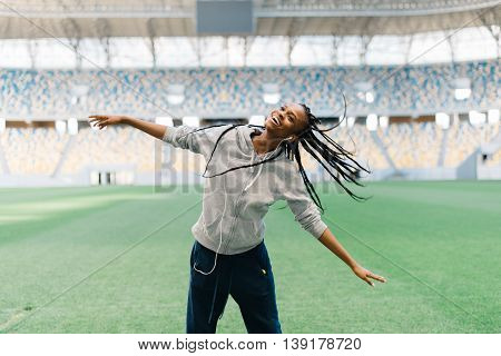Attractive african american female dancing swinging her braided hair at empty stadium.