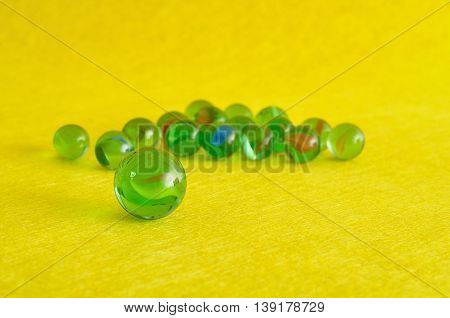 A collection of green marbles isolated on a yellow background with shallow depth of field