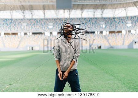 Cute african american female in sportswear dancing swinging her braided.