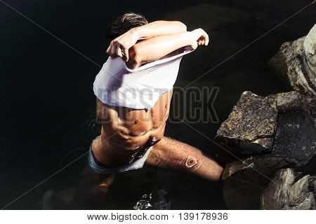 handsome young macho man with muscular sexy body and six packs on torso in pants and wet shirt sunny day outdoor on water natural background