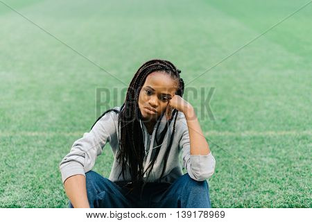 Sporty african american woman sitting down with hand on head and feeling disappointed against green grass at stadium.