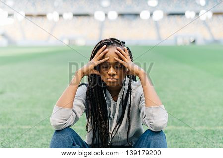 Tired pretty african american young woman sitting with legs crossed and having headache, stadium at background.