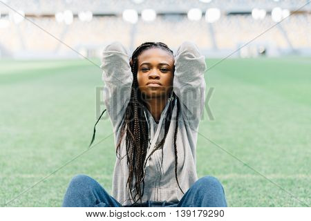 Unhappy and frustrated african american woman sitting with her hands behind her head on the green grass.