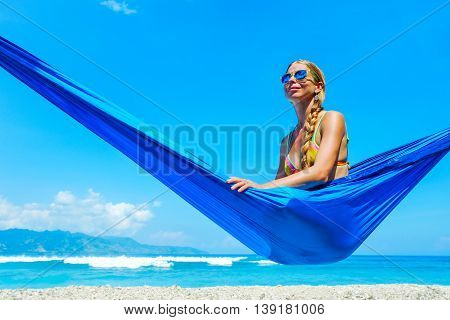 Beautiful beach. Girl relaxing in hammock on the tropical beach. Summer holiday and vacation concept.