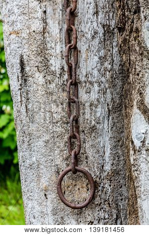 Old rusty chain on a weathered wooden post