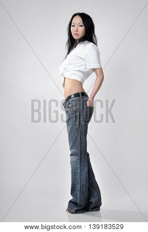 Girl in tall jeans on white background