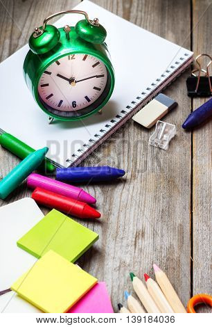 Still life, business, education concept. Assortment of office and school supplies and alarm clock on a rustic wooden table. Selective focus, copy space background
