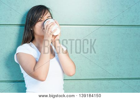 Young Woman Drinking Coffee From Takeaway Mug