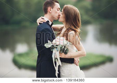 Romantic wedding couple, man and wife, posing near beautiful lake.