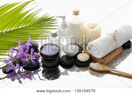 Still life with orchid and oil, towel and palm