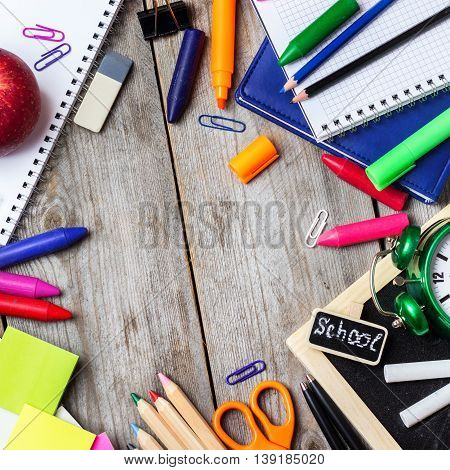 Still life, business, education concept. Assortment of office and school supplies, alarm clock and chalkboard on a rustic wooden table. Selective focus, copy space background, top view
