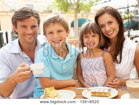 Young Family Enjoying Cup Of Coffee And Cake In Cafe Together