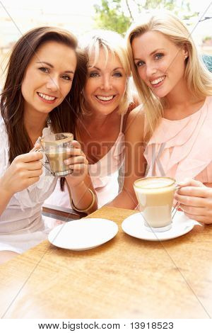 Three Women Enjoying Cup Of Coffee In Cafe