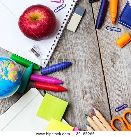 Still life, business, education concept. Assortment of office and school supplies and alarm clock on a rustic wooden table. Selective focus, copy space background, top view