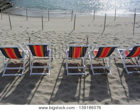 Row of colorful wooden chairs at Marina di Pisa sand beach . Tuscany Italy