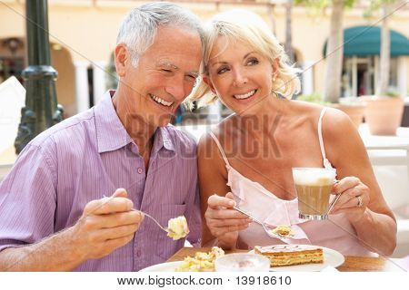 Senior Couple Enjoying Coffee And Cake In Cafe