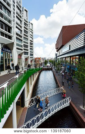 Zaandam Netherlands - July 02 2016: Some people are walking on a central street build up with traditional Dutch houses