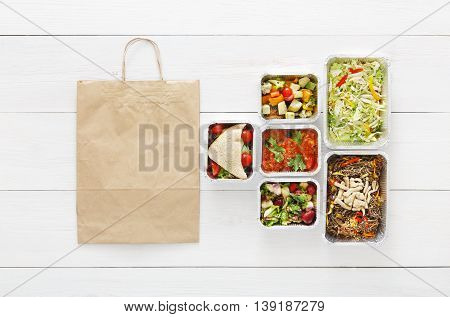 Healthy food delivery. Take away of natural organic low carb diet. Fitness nutrition in foil boxes cutlery and brown paper package bag. Top view flat lay with copy space at white wood