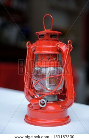 Red kerosene lamp on the table .