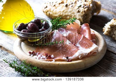 Thin Slices Of Prosciutto With  Olives On Wooden Background