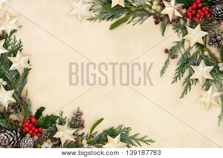 Christmas abstract background border with gold star decorations, holly, mistletoe and snow covered cedar cypress on parchment paper.