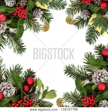 Christmas background border with red bauble decorations, holly, ivy, snow covered pine cones and fir leaf sprigs over white.