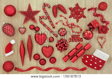 Red Christmas tree decorations and baubles over light oak background.