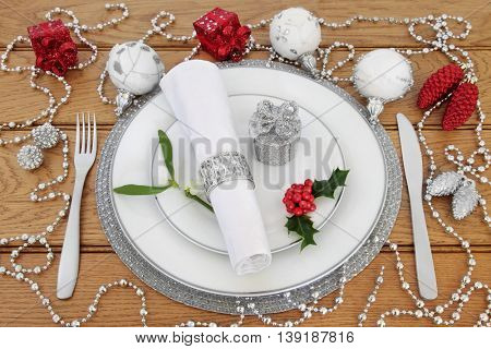 Christmas dinner place setting with white porcelain plates, knife and fork, linen serviette with silver ring, bauble decorations, holly and mistletoe over oak background.