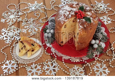 Panettone christmas cake and slice, holly berries, silver snowflake glitter decorations with bead strands over oak table background.