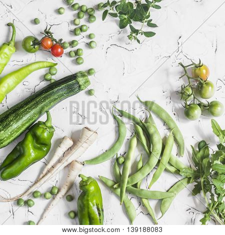 Fresh raw green vegetables - zucchini green peas and beans parsnips peppers tomatoes onions on a white background. Healthy Vegetarian vegan table