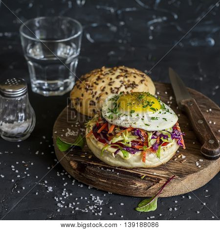 Homemade burger with fried egg and coleslaw on rustic wooden board on a dark stone background. Healthy delicious food